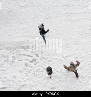 Elevated view of family play in snow covered parking lot - Stock Photo