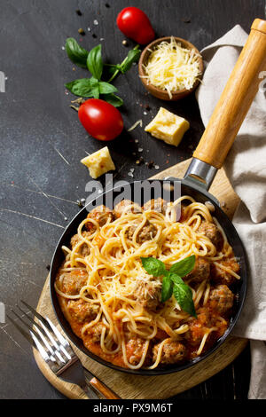 Spaghetti with Meatballs with Tomato Sauce and Parmesan Cheese on a dark stone or concrete background. Copy space. - Stock Photo