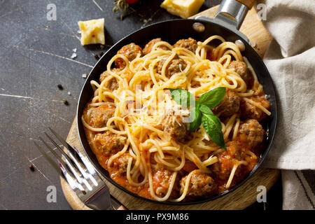 Spaghetti with Meatballs with Tomato Sauce and Parmesan Cheese on a dark stone or concrete background. - Stock Photo
