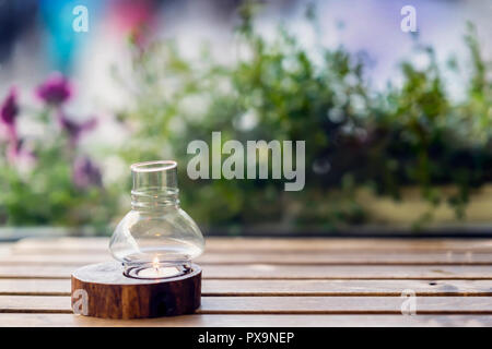Candle in a candlestick on a wooden table and street violet flowers behind, copy space - Stock Photo