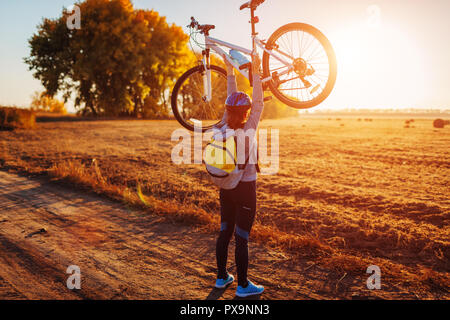 Young bicyclist raising her bicycle in autumn field at sunset. Happy woman celebrates victory holding bike in hands. - Stock Photo