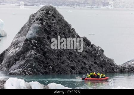 Boat amongst calved ice from the Breidamerkurjokull glacier in Jökulsárlón glacial lagoon, Iceland. - Stock Photo