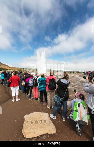 Tourists watch the eruption of the Strokkur geyser, Haukadalur valley, Hvítá River, Iceland. - Stock Photo
