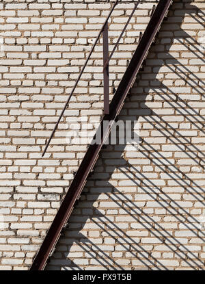 fire escape on a brick wall background of a building, sunny weather - Stock Photo