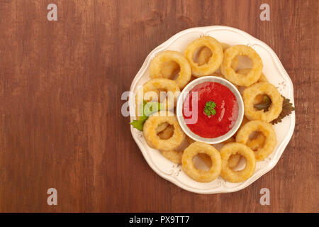 A photo of squid rings with a tomato sauce, shot from the top on a dark rustic wooden background with copyspace - Stock Photo