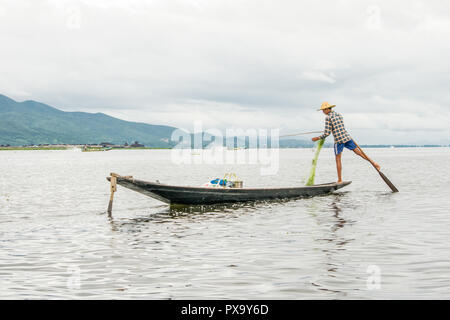 Travel local young Burmese male fisherman wearing checked shirt, using stick and net to fish, balancing on one foot on boat, Inle Lake Myanmar, Burma - Stock Photo