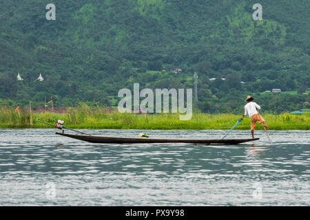 Travel, local fisherman in white shirt and orange shorts balancing on one foot on the tip of the boat and pulling net to collect fish, Inle Lake Burma - Stock Photo