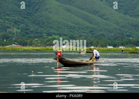 Young fisherman with net, crouching squat on a long boat, balancing. traditional boat and fishing techniques. Inle Lake, Shan region, Myanmar, Burma - Stock Photo