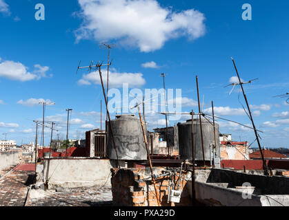 Antennas on the roofs against a blue sky - Stock Photo
