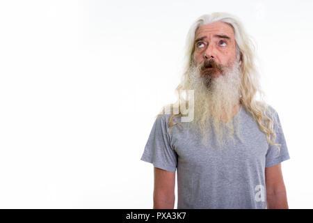 Studio shot of senior bearded man thinking while looking up - Stock Photo