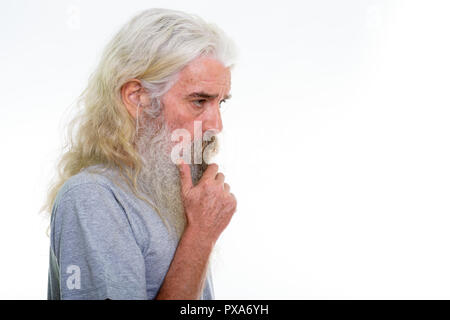 Profile view of senior bearded man thinking with hand on chin - Stock Photo