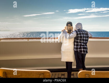 Casually dressed couple on Alaskan Inside Passage cruise looking out to open ocean from a sunlit exterior ship deck. - Stock Photo