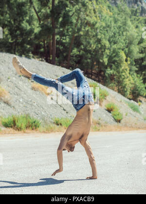 Young man break dancing on the road. - Stock Photo