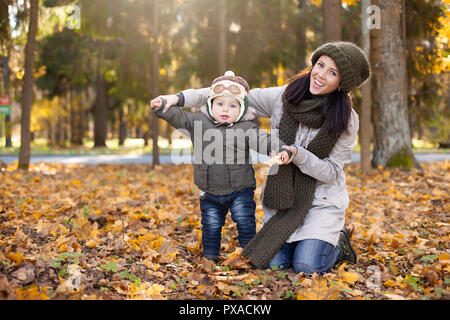 little boy in the pilot cap standing with his mother and showing wings , yellow and orange foliage around him. Autumn - Stock Photo