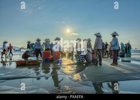 Fish market session seas scene people gathered inside basket fish sale, strenuous rowing fishermen fish brought ashore fishing village - Stock Photo