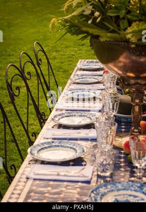 Elegant set table in garden for dinner or wedding. - Stock Photo