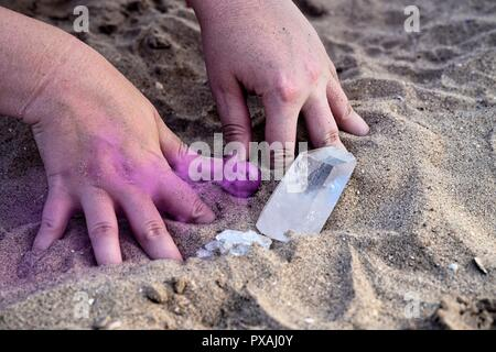 Hands playing in the sand with smoke bombs and crystals - Stock Photo