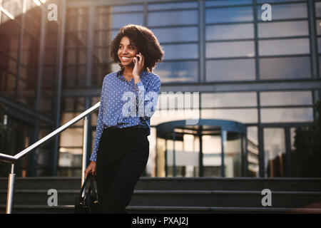 Woman walking down the steps outside office building and talking on mobile phone. Businesswoman talking on cell phone with office building in backgrou - Stock Photo