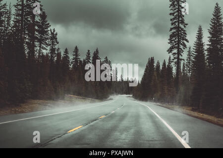On the road with stormy and cloudy weather in the Cascade Range, near Diamond Lake, Oregon, USA. - Stock Photo