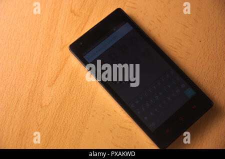 A black mobile on a table of agglomerate with imitation of beech wood with space for messages and posters - Stock Photo