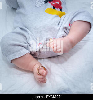 Gold wedding rings on the toes of the new born baby's legs - Stock Photo