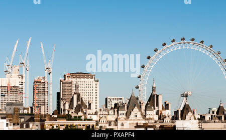 London skyline on a clear blue day with the London Eye and construction on display - Stock Photo