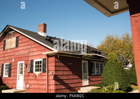 Small red house with roof and top floor destroyed by fire - Stock Photo