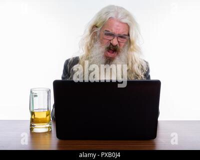Studio shot of angry senior bearded businessman shouting while u - Stock Photo