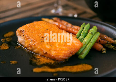 Salmon serviced on a plate with carrots and asparaguses on a black plate. - Stock Photo