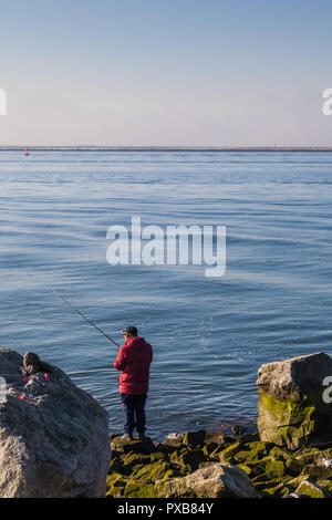 Man in a red jacket fishing the south arm of the Fraser River - Stock Photo