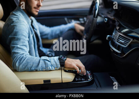 awesome man is sitting with opened door in the vehicle - Stock Photo