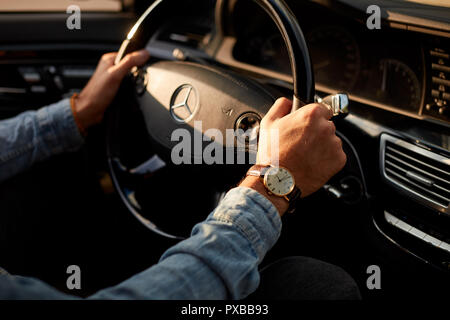 male's arms on the steering wheel - Stock Photo