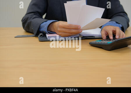 man calculate domestic bills. Businessman using calculator checking balance & costs. Startup counting finance for paying taxes at office - Stock Photo