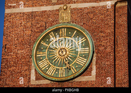Wawel Cathedral clock on bell tower in Krakow, Poland, gilded sun in the middle and Roman numerals, dating back to 17th century. - Stock Photo
