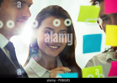 Happy girl works with colleagues in office with post it notes in foreground. Concept of teamwork and partnership - Stock Photo