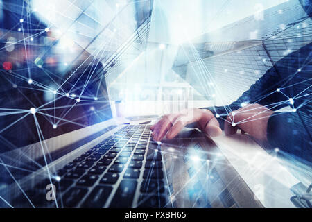 Business man works in office with laptop in the foreground. Concept of teamwork and partnership. double exposure with network effects - Stock Photo