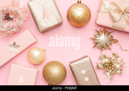 Pink and gold christmas gifts isolated on pastel pink background. Wrapped xmas boxes, christmas ornaments and baubles. Christmas mock up. - Stock Photo