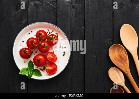 Various wooden spoons and tomatoes in a plate with Himalayan salt, pepper and basil on black wooden table. Top view with copy space for menu or recipe - Stock Photo