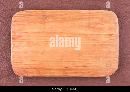 Frame made of plank lies on dark brown natural leather. Texture of a tree. View from above. - Stock Photo