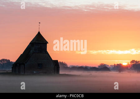 Sunrise and orange cloudy sky over the lonely Thomas a Becket church at Fairfield on Romney Marsh. Fields covered in mist, laying the landscape. Some sheep and cows in the mist. - Stock Photo