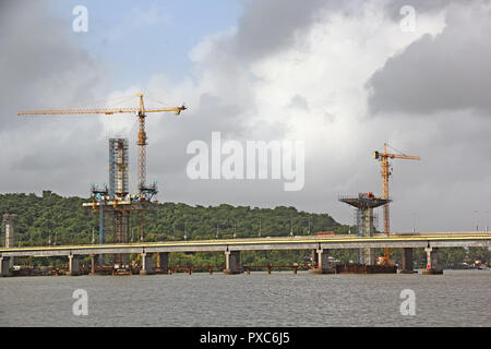 Construction of cable stayed bridge progressing from tall central concrete piers with the aid of tower cranes for the third bridge over Mandovi River - Stock Photo