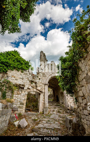 Springtime landscape of the ruins of Stari Bar ancient fortress, walking on arch way to ruined defense tower, in the medieval town of Bar in Montenegr - Stock Photo
