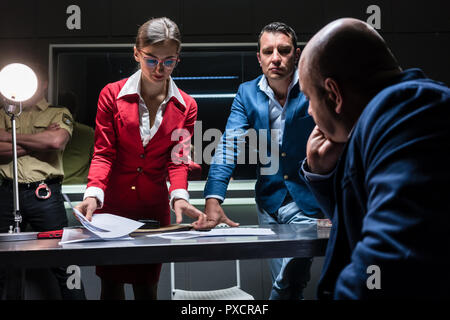 Two persuasive investigators trying to obtain a confession - Stock Photo