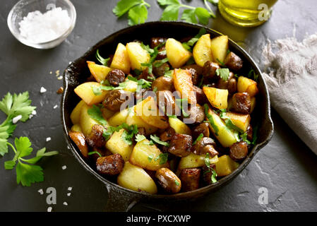 Close up of fried potatoes with mushroom and sausage in frying pan on black stone table - Stock Photo