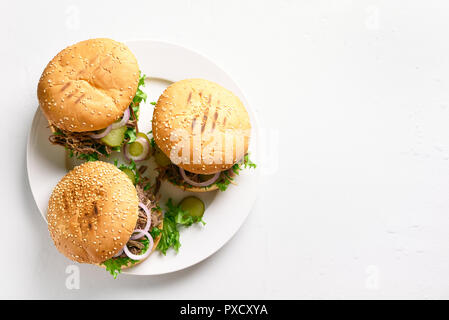 Pulled beef hamburger with vegetables on white plate over stone background with copy space. Top view - Stock Photo