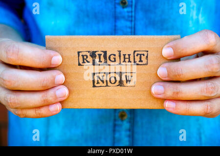 Woman hand holding cardboard card with words Right Now made by black alphabet stamps. Denim backgrounds. - Stock Photo