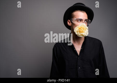 Young handsome man against gray background with flower in mouth - Stock Photo