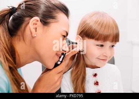Smiling doctor examining child ear using Otoscope - Stock Photo