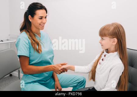 Friendly doctor shaking little girl's hand in office - Stock Photo
