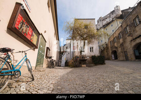 Salzburg, Austria - April 6, 2018: View of empty street in the old town of Salzburg. Medieval street with old buildings, parked bicycles and old grani - Stock Photo